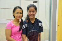 Photo of two girls holding squash rackets